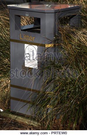 Litter bin amongst plants in a public garden in Salisbury, Wiltshire, England, UK - Stock Photo