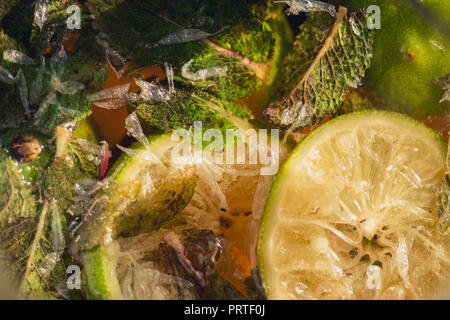 Carbonated soda water or juice with lime and mint in a glass jug. Macro closeup - Stock Photo