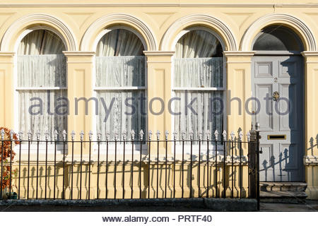 Arched front door and windows of a rendered and painted house in Blandford Forum, Dorset, England, UK - Stock Photo