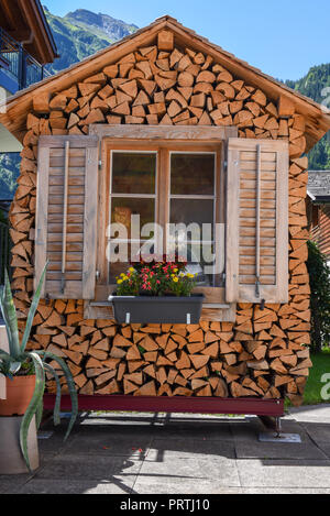 House built with tree trunks at Engelberg on the Swiss alps - Stock Photo
