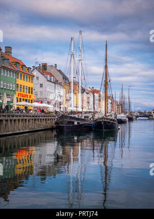 Nyhavn - with its picturesque harbour with old sailing ships bobbing on the canals' water, and colourful facades of old houses is a 17th-century water - Stock Photo