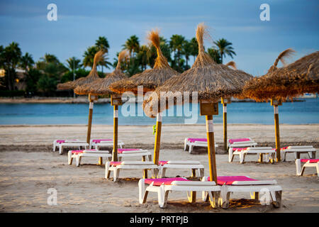 Empty chairs and straw umbrellas on the Alcudia beach in Majorca - Stock Photo