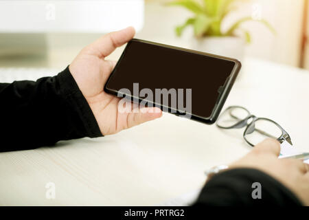 Portrait of man is holding pen in one hand. Portrait man showing phone in one hand with glasses on table. - Stock Photo