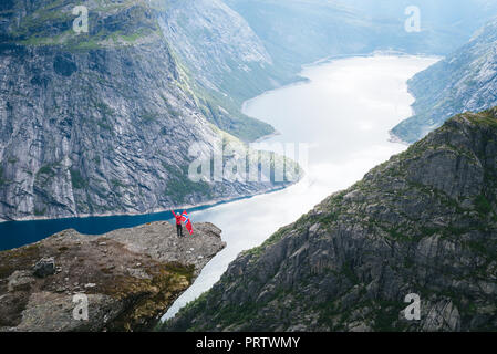 Tourist with Norwegian flag. Ringedalsvatnet Lake. View from cliff near Trolltunga. Tourist attraction of Norway - Stock Photo