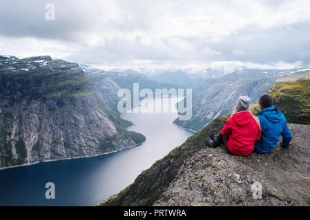 Ringedalsvatnet Lake near Trolltunga. One of Norway most spectacular sight. Couple travelers sits on rock and enjoys a beautiful view - Stock Photo