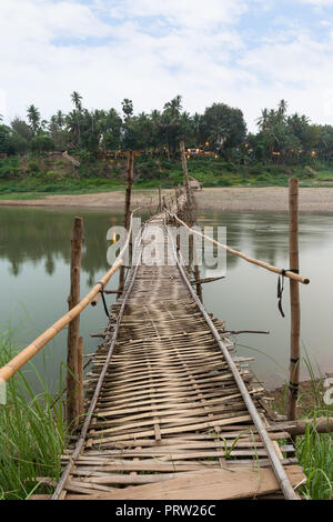 Wooden bamboo bridge over Nam Khan River at low tide viewed from the front in Luang Prabang, Laos. - Stock Photo