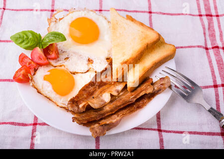 Breakfast with bacon and fried eggs. Served on white plate with sliced cherry tomato, basil leaves and crispy toast slice. - Stock Photo