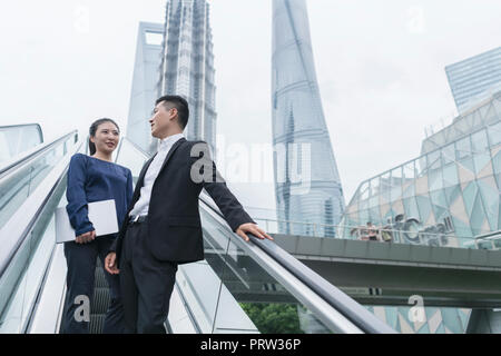 Young businesswoman and man talking while moving up city escalator, Shanghai, China - Stock Photo