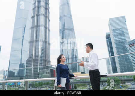 Young businesswoman and man talking in city financial district, Shanghai, China - Stock Photo