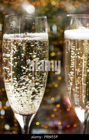Two Champagne Flutes on Christmas Background with Xmas Tree - Stock Photo