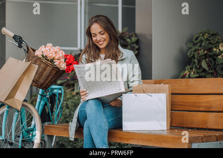 Happy young woman reading newspapers while sitting on the bench in the city - Stock Photo