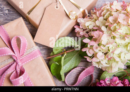 Flowers composition. Workspace with rose flowers, gift, paper bag. Top view, flat lay. - Stock Photo