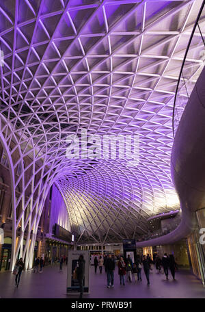 Kings Cross railway station, London, UK, September 30th 2018 - The lattice ceiling of the booking hall at night is lit with purple light. - Stock Photo