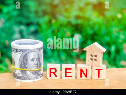 Wooden house, money with the inscription rent. Rental of property, apartments. services of a realtor. affordable housing, rental prices. real estate - Stock Photo