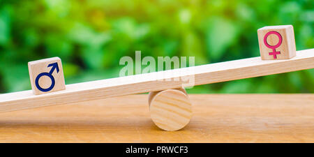 Figures of a man and a woman on the scales. inequality concept : man and women on a weighing balance, gender pay gap. divorce. Division of property in - Stock Photo