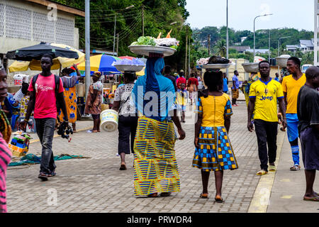 SEKONDI TAKORADI, GHANA – 10 APRIL 2018: Women in colorful dress carry baskets of produce on their heads ready to sell at busy Bosomtwi Sam Fishing Ha - Stock Photo
