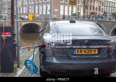 Tesla recharging in the canal district of Amsterdam - Stock Photo
