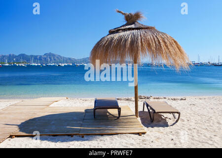 Chairs and umbrella on the beach in Port de Pollenca, Majorca, Spain - Stock Photo