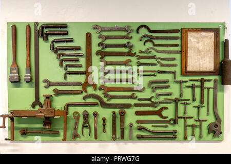 A carefully arranged tool board, in an old factory, rusty spanners and measuring equipment, 1930 - Stock Photo