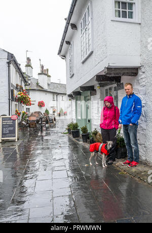 Hawkshead, Lake District, Cumbria. 4th Oct 2018. U.K. Weather. Hawkshead, Lake District, Cumbria, England. 4th October 2018. Tourists visiting the small town of Hawkshead in the lake district take shelter from the heavy rain shower that hits mainy parts of the U.K. Alan Beastall/ /Alamy Live News Credit: Alan Keith Beastall/Alamy Live News - Stock Photo