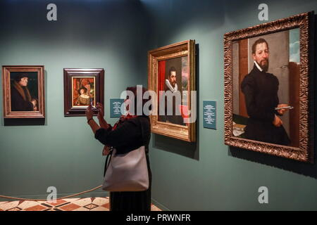 ST PETERSBURG, RUSSIA - OCTOBER 4, 2018: A visitor looks at paintings Portrait of John Chambers by German artist Hans Holbein the Younger, Portrait of a Young Man by German-Swiss ARTIST Ambrosius Holbein, Portrait of a Young Man (Francesco Bassano?) by Italian painter Domenico Tintoretto, and Portrait of Orator Giovan Pietro Maffei by Italian painter Giovanni Battista Moroni, from left, at an exhibition titled 'Imperial Capitals: St Petersburg - Vienna. Masterpieces of Museum Collections' at the Hermitage. The exhibition is a joint project by the State Hermitage and the Vienna Kunsthistorische - Stock Photo