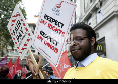 London, Greater London, UK. 5th Oct, 2018. A man seen standing next to a poster saying Respect my rights, respect my Union and Fair pay during the protest.Wetherspoons, TGI Fridays, and McDonald's workers rally together in London to demand better working conditions and a fair pay in the hospitality industry. Credit: Andres Pantoja/SOPA Images/ZUMA Wire/Alamy Live News - Stock Photo