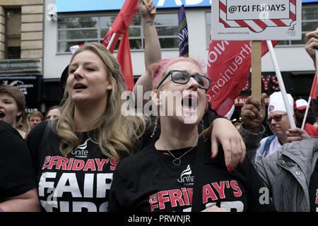 London, Greater London, UK. 5th Oct, 2018. Two women seen wearing black T-shirts with the TGI Fridays logo asking for fair tips in their workplace during the demonstration.Wetherspoons, TGI Fridays, and McDonald's workers rally together in London to demand better working conditions and a fair pay in the hospitality industry. Credit: Andres Pantoja/SOPA Images/ZUMA Wire/Alamy Live News - Stock Photo