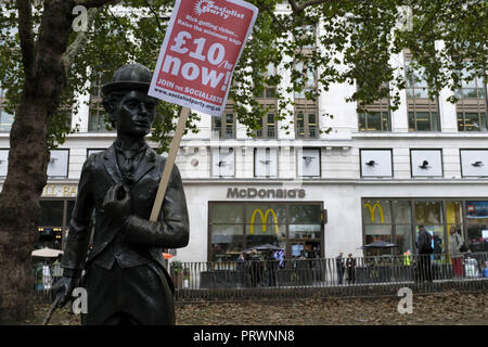 London, Greater London, UK. 5th Oct, 2018. A Charles Chaplin sculpture seen holding a poster saying £10/hr Now! during the protest.Wetherspoons, TGI Fridays, and McDonald's workers rally together in London to demand better working conditions and a fair pay in the hospitality industry. Credit: Andres Pantoja/SOPA Images/ZUMA Wire/Alamy Live News - Stock Photo