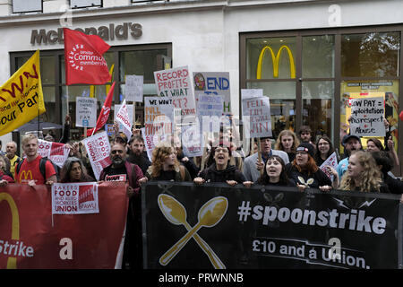 London, Greater London, UK. 5th Oct, 2018. Protesters seen holding banners and flags outside Mc Donalds during the protest.Wetherspoons, TGI Fridays, and McDonald's workers rally together in London to demand better working conditions and a fair pay in the hospitality industry. Credit: Andres Pantoja/SOPA Images/ZUMA Wire/Alamy Live News - Stock Photo