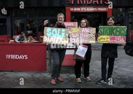 London, Greater London, UK. 5th Oct, 2018. Protesters seen holding posters in front of a TGI Fridays during the protest.Wetherspoons, TGI Fridays, and McDonald's workers rally together in London to demand better working conditions and a fair pay in the hospitality industry. Credit: Andres Pantoja/SOPA Images/ZUMA Wire/Alamy Live News - Stock Photo