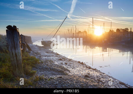 Oare Creek, Kent, UK. 5th October 2018: UK Weather. A misty Autumn sunrise as the tide starts to come in and cover a sunken abandoned yacht at Oare Creek near Faversham in Kent. Credit: Alan Payton/Alamy Live News - Stock Photo