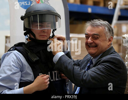 05 October 2018, North Rhine-Westphalia, Cologne: Herbert Reul (CDU, r), North Rhine-Westphalia's Interior Minister, helps a policewoman put on a ballistic helmet. The new special helmet protects policemen from shots, stings, acids and flames. Photo: Oliver Berg/dpa - Stock Photo