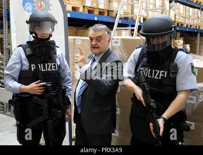 05 October 2018, North Rhine-Westphalia, Cologne: Herbert Reul (CDU, M), North Rhine-Westphalia's Interior Minister, stands between two police officers wearing ballistic helmets. The new special helmet protects policemen from shots, stings, acids and flames. Photo: Oliver Berg/dpa - Stock Photo
