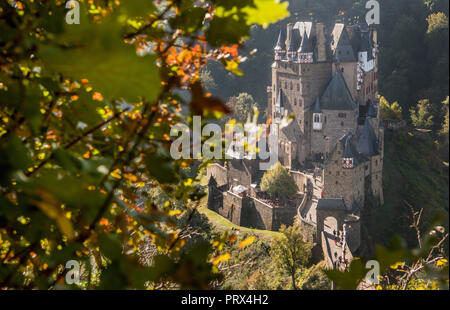 05 October 2018, Rhineland-Palatinate, Wierschem: The sun prevails over the last fog banks at Burg Eltz, while the leaves of the trees turn autumnal. In the coming days the temperature is expected to reach 23 degrees. The medieval castle complex is one of the main tourist attractions in Rhineland-Palatinate and is the starting point for numerous hiking trails through the Eifel. Photo: Boris Roessler/dpa - Stock Photo
