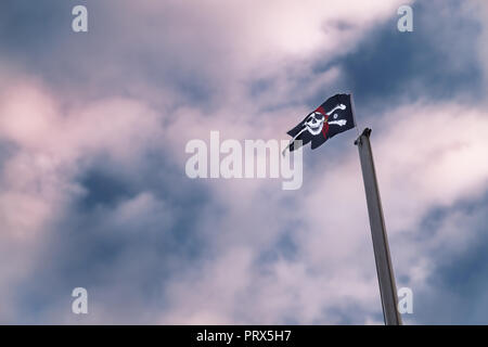 Pirates flag on mast against dramatic, blue red cloudy sky - Stock Photo