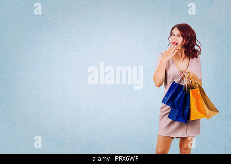 Young redhead woman, wearing pink dress, holding shopping bags, hand covering mouth, surprised emotion isolated on blue background with copy space. - Stock Photo