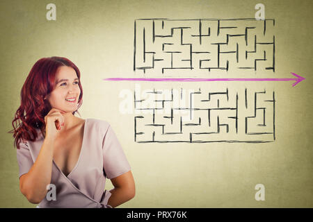 Young redhead pensive woman holding hand under chin thoughtful looking to find a solution to escape from maze. Young businesswoman breaking the rules, - Stock Photo