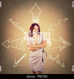 Redhead woman standing with arms crossed and arrows pointed to different directions over colorful background. Difficult choice, decide which way to go - Stock Photo