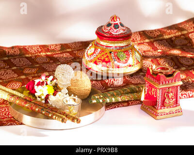 A STILL LIFE OF DASSERA FESTIVAL OBJECTS IN MUMBAI INDIA SHOWING A KALASH/POT, DIYAS, SWEETS, BANDHANI, SAREE, SILVER THALI WITH COCONUT, DIYA, FLOWER - Stock Photo