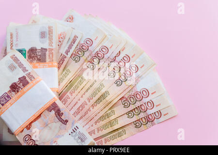 The pack of five thousandth ruble notes in half a million Russian rubles in the banking package is on the background of scattered banknotes.financial and banking concepts.Copy space - Stock Photo