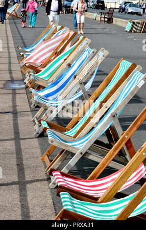 Colourful row of deckchairs on the seafront at Sidmouth east Devon England UK - Stock Photo