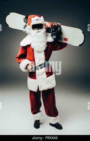 santa claus in ski mask holding snowboard over shoulder on grey background - Stock Photo