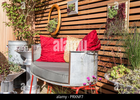 repurposed recycled metal garden seat with cushions, unusual metal containers, various succulents and sempervivum plants growing in wooden frames on c - Stock Photo