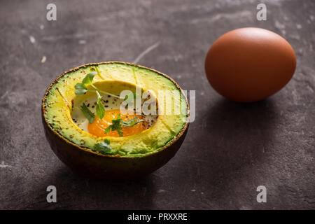 Homemade Organic Egg Baked in Avocado with Salt and Pepper - Stock Photo