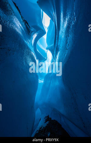 From inside the depths of a narrow winding canyon cut through the ice of hte Matanuska Glacier. Lit to show detail in the ice with rock below - Stock Photo