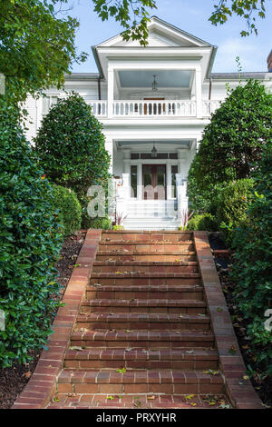 JONESBOROUGH, TN, USA-9/29/18: A set of brick steps leads up to an elegant white, two-story, 19th century home. - Stock Photo