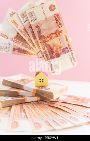 small house model is above russian rubles, the concept of home buying and selling.The concept on the search and purchase of real estate. House hunting.five thousand bill isolated on pink background. - Stock Photo