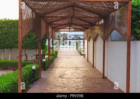 passage to the pool under a wooden gazebo in the hotel - Stock Photo