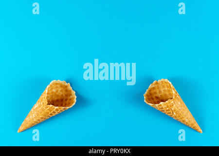 Creative summer layout made of ice cream cones, waffle cones on bright light blue background. Minimal concept - Stock Photo