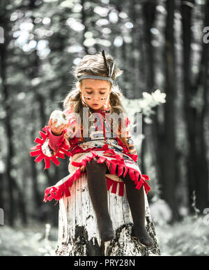 little cute girl in costume of American Indian ,plays near a tree and eating an Apple ,the concept of children and childhood - Stock Photo
